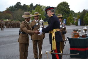 Reviewing Officer, Maj Gen T B Radford DSO OBE presenting the QOGLR Champion Trophy to the QOGLR Champion Recruit