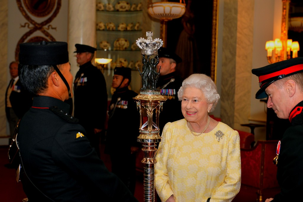 Queen Elizabeth II admires the ornate Gurkha Truncheon (ceremonial staff), which is the Gurkha Rifles equivalent of a regimental Colour (battle flag) and was given to the Rifles by order of Queen Victoria in 1863, during a viewing of the truncheon in the Bow room at Buckingham Palace in London.