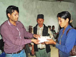 Diktel Municipality officer Narayan Dhakal handing over ID card to an earthquake victim along with  relief amount to build shelter at a programme organised in the municipality office, in Khotang, on Sunday. Photo: THT