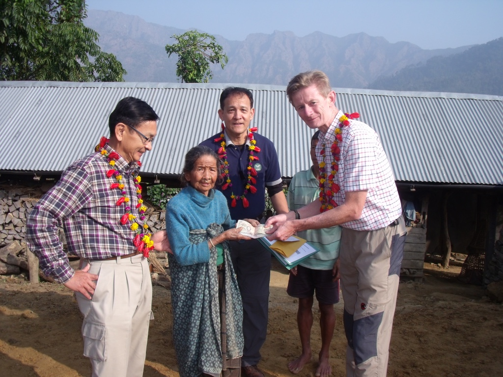Widow Chandrakali Thapa receiving a grant for home rebuilding from John White
