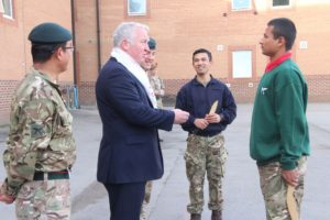 Training Rifleman David Gurung receiving coin from the Minister Armed Forces